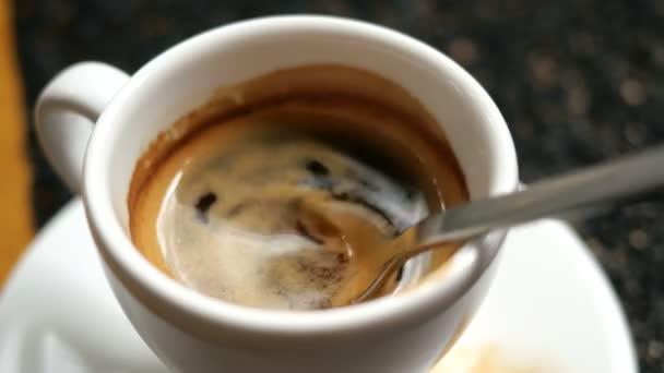 Fekete, forró Espresso kávé bolyhos hab kevert fém teáskanál egy fehér kávéscsésze.