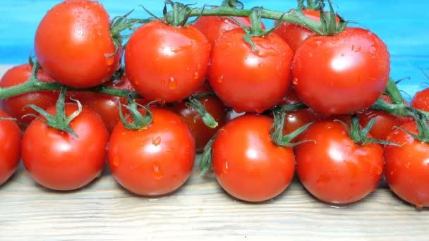 Kirschtomaten auf den Zweigen, die auf dem Küchentisch liegen, streuen oder gießen Wasser oder Chemikalien. kann vor Gebrauch verarbeitet werden. Tropfen auf Tomaten.