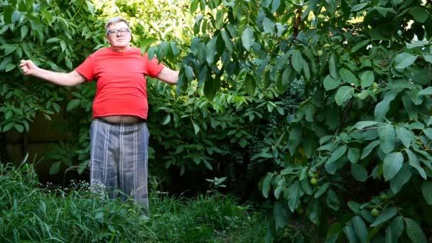 Starší muž v příležitostných šatech, možná důchodce, cvičení nebo gymnastika na dvorku nebo na zahradě. Použití jako zdravý životní styl pro lidi středního věku.