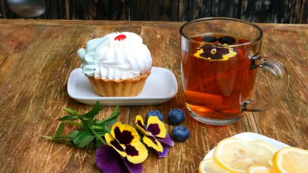 Child hand takes with teaspoon tasty fresh cake on saucer, on wooden table. On table there is also cup with tea, pansy flowers and saucer with lemon.