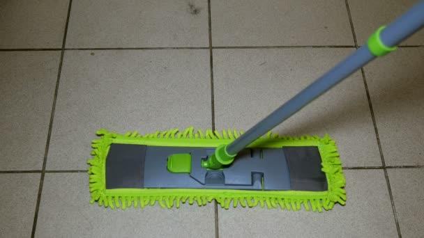häusliches Leben. Fliesenbodenreinigung mit modernem Flachmopp mit praktischem Drehgriff. Konzept der Hausarbeit. Nahaufnahme.