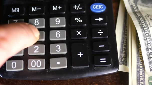 Human fingers of hand make counts of money - amerikan dollars, which lie nearby, on calculator. The concept of keeping records of home finances or business profits.