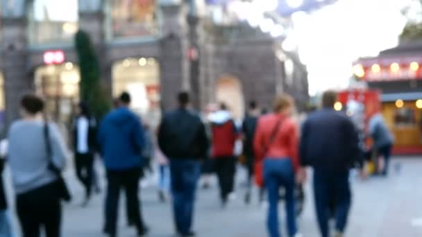 Crowd of unidentified people walk along Khreshchatyk Street on weekend in Kiev city in Ukraine, during Covid-19 coronavirus epidemic. Defocused video. Blurred motion. Wide plan.
