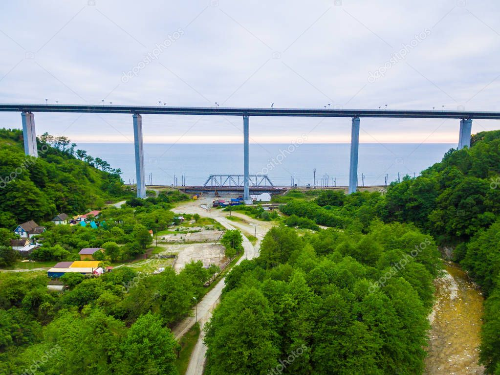 Drone view of the Zubova Schel viaduct between mountainsides with forest on the background of the sea in overcast summer day, Sochi, Russia