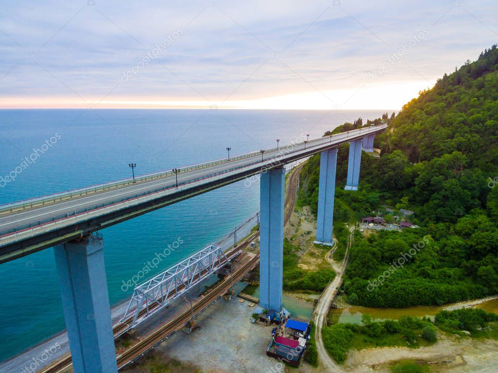 Drone view of the Zubova Schel viaduct and mountainside with forest on the background of the sea in overcast summer day, Sochi, Russia