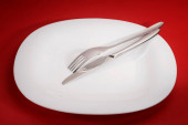 White empty square plate with fork and knife on red table