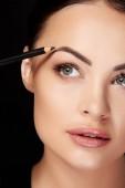 Beauty koncept, mladá žena, make-up, malování obočí s černou tužkou, černé pozadí