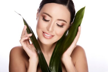 Beautiful and natural young woman posing with green leaves isolated over white background, skin care concept, hydrated skin stock vector