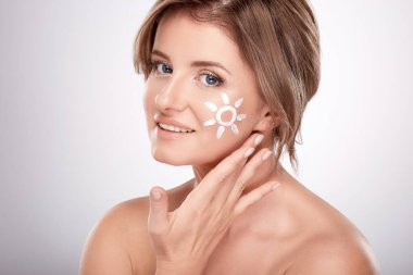 pretty smiling young woman using facial cream at grey background, beauty photo, skin care, spa concept