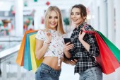 Fotografie pretty young women posing with colorful shopping bags at shopping mall