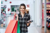 Fotografie beautiful brunette young woman with colorful shopping bags using mobile phone, online shopping concept