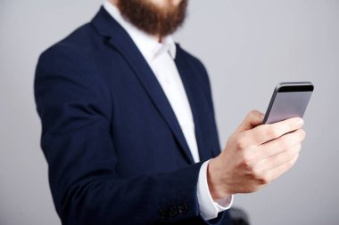 cropped photo of businessman holding mobile phone in hand