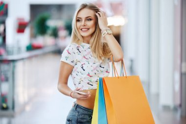 beautiful blonde young woman with colorful shopping bags in shopping mall