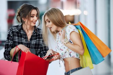 pretty young women with colorful shopping bags at shopping mall