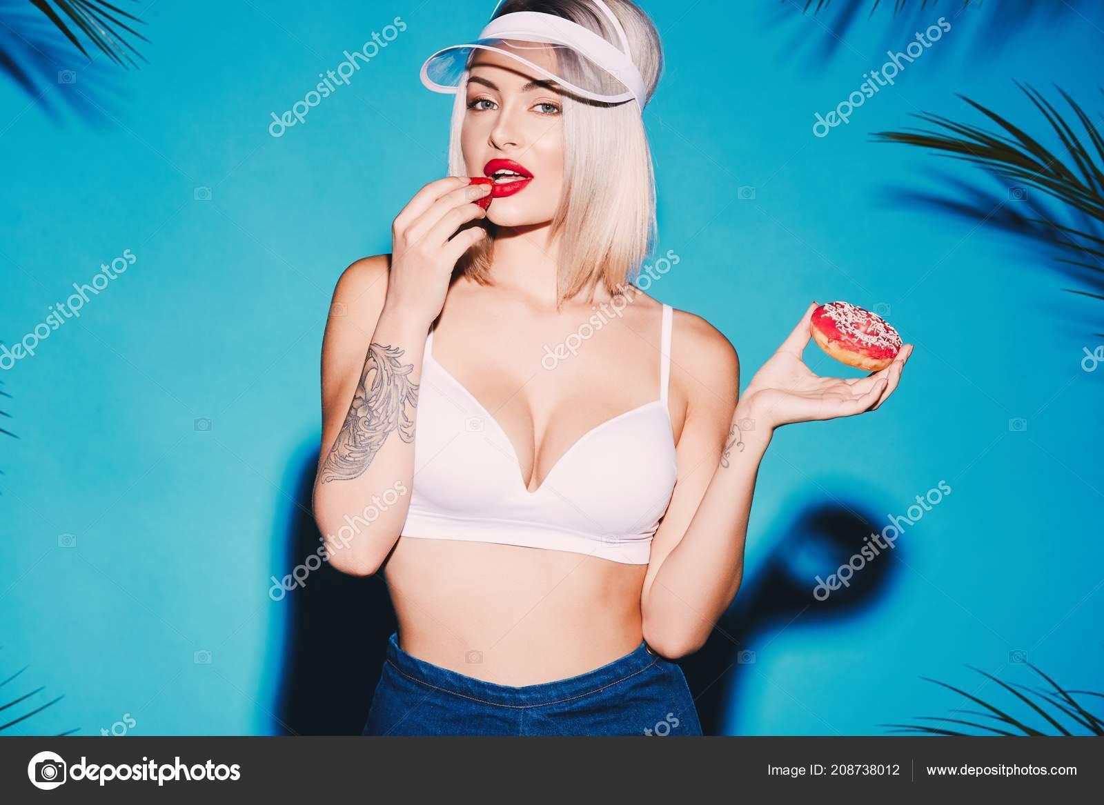 23ebefb753ee Chica sexy con cabello rubio, vestida con top y cap holding donut y morder  el pie de fresa sobre fondo azul con hojas de Palma — Foto de VelesStudio