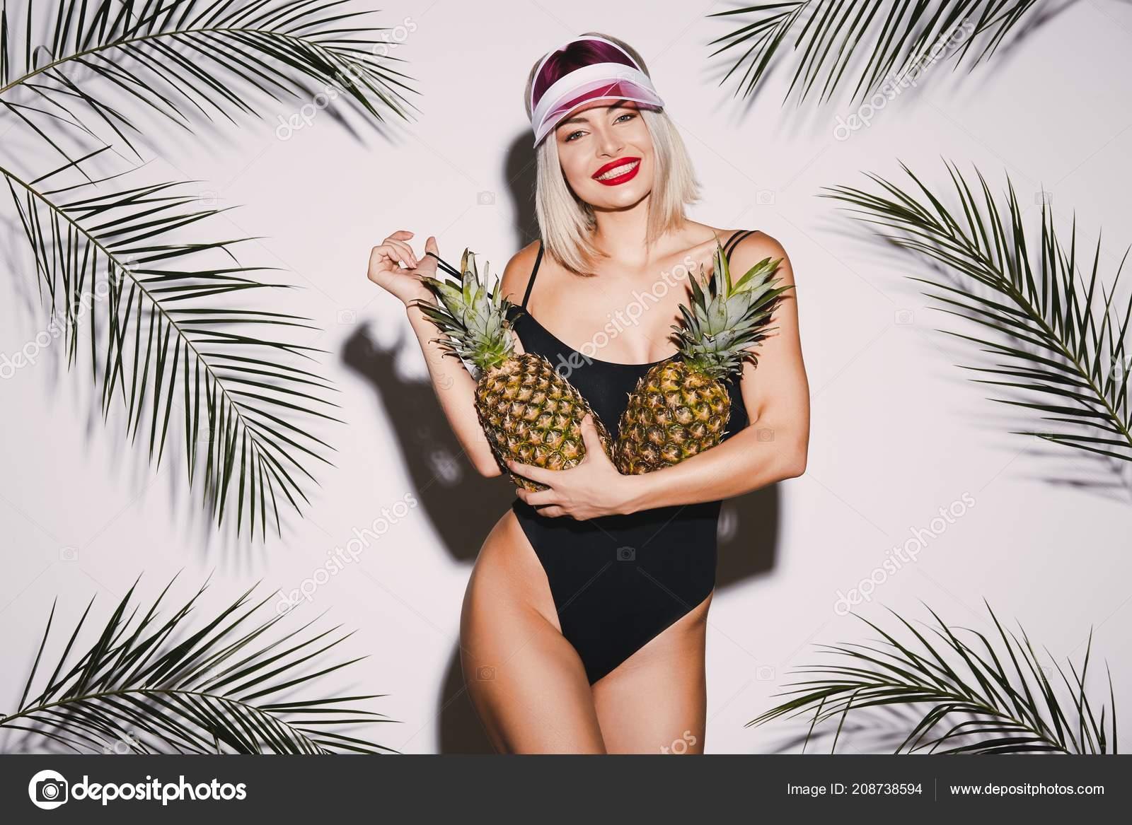 c4d1253aa Linda menina com cabelo loiro vestindo preta de natação terno e cap-de-rosa  em pé de ananás no fundo branco do estúdio com palmas