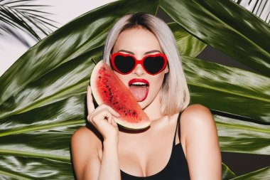 Hot girl with blonde hair wearing black swimming suit and sunglasses standing on palm leaves background posing with watermelon slice and red lips, licking