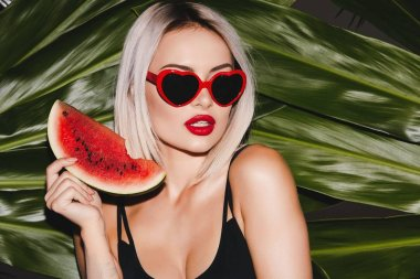 blonde woman wearing sunglasses standing on palm leaves background with watermelon slice