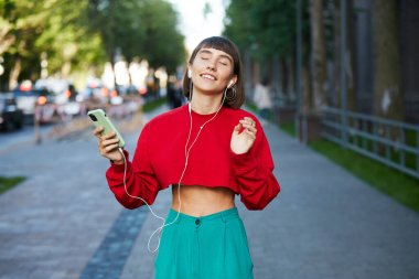 lovely girl standing on the street with earphones and listen music, cute millenial woman in red stylish sweater holding smartphone and listening music