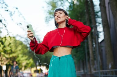emotinal girl listening music on the street, cute millenial woman in red stylish sweater having using earphones and listen music