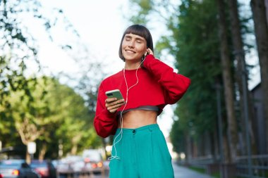 beautiful emotional girl listening music on the street, cute millenial woman in red stylish sweater using erphones on the modern city background