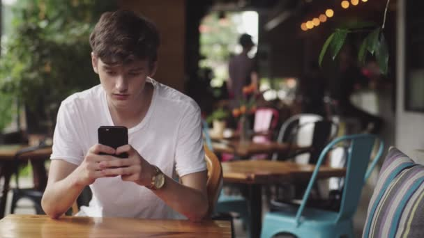 Young Man surfing internet in mobile phone, handy touch and sending text message in cafe. Handsome Teenager chatting in mobile app in public place.
