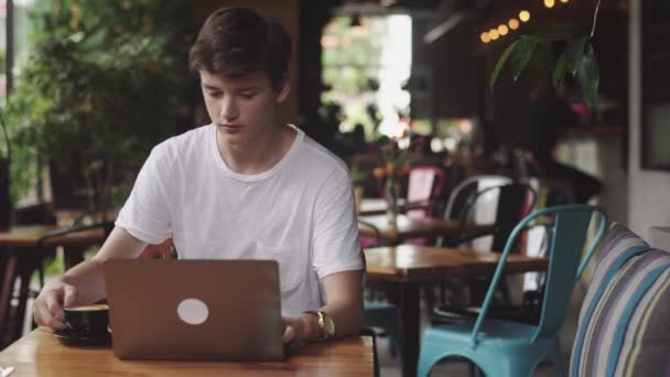 Young man surfing website and chatting, freelancer and blogger working as a graphic designer indoor, and drinking coffee, modern working place sitting in cafe. Open laptop in restaurant.