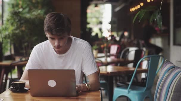 Fiatalember szörfözés weboldal és beszélgető, szabadúszó és blogger dolgozik, mint egy grafikus Designer beltéri, modern dolgozó helyen ülve kávézóban. Nyílt laptop az étteremben.