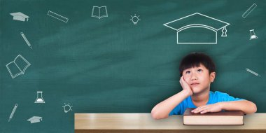 Education concept, Boy sitting with books on the table freehand chalk drawing graduation hat on green chalkboard background celebrating educational success. With space for your message.