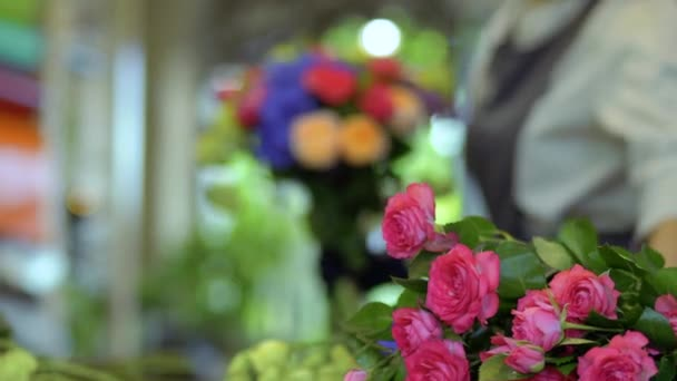 Florist creating flower bouquet at blurred background of roses