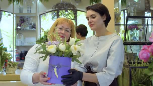 Florist and her assistant demonstarate complete flower composition