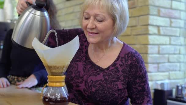 Granny Chaude granny-barista verser l'eau chaude à l'intérieur de la verseuse à