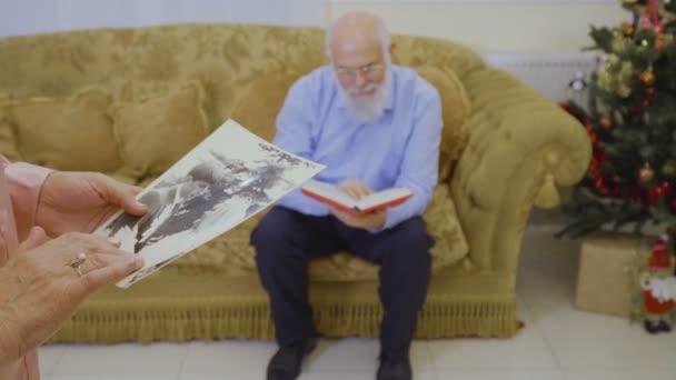 Érett nő meg a régi fényképeket az előtérben. A férje ül a kanapén, a háttér, és olvassa el a könyvet. Idősebb ember vegye le a szemüveget, és nézze meg a felesége.