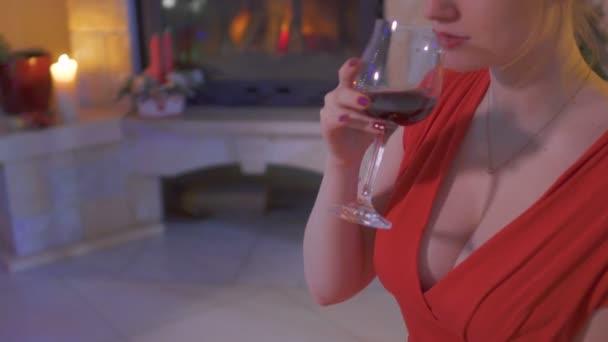 Mladá žena v červených šatech s otevřít dekolt, pití červeného vína. Ochutnejte vína u krbu se svíčkami. Rozmazané pozadí