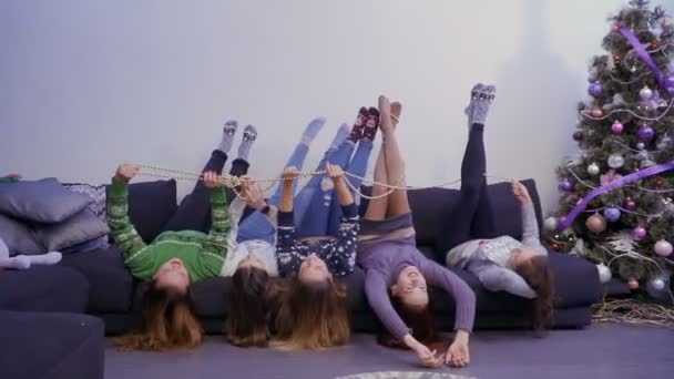 Young and carefree girls lies on sofa upside down and have fun