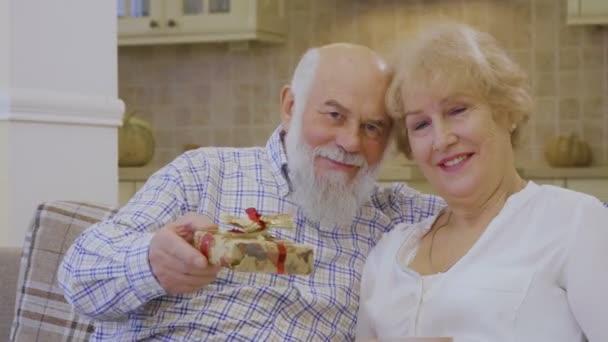 Šťastný starší pár sedí na gauči doma. Starší muž objímá svou ženu, staří lidé vypadá ve fotoaparátu a usměje se. Šedovlasý muž drží v ruce vánoční dárek a Ukázat na kameru. Šťastná rodina