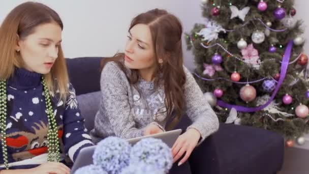 Two young girlfriends in sweaters sits on sofa at home and makes online Christmas purchases in the internet store. Attractive girls are relaxing together at home and prepares to the holidays.