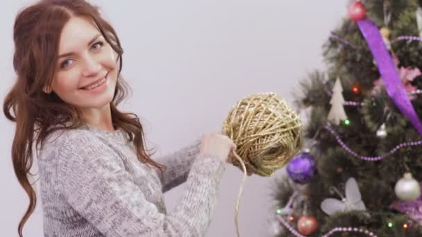 Young woman decorate Christmas tree before New Year Eve