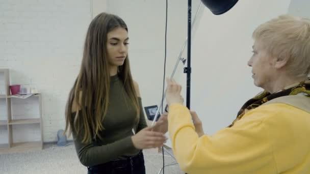 Fotósok fehér fotó stúdióban dolgozik, és hogy a fénykép a táblázat fölött. Folyamat, hogy a fénykép a stílusos elemekkel
