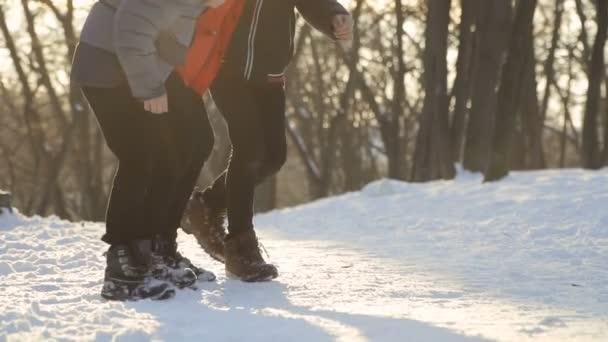 Jumping legs of three boys, slow motion, winter park