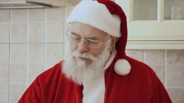 Santa Claus v červený kostým sedí na kuchyňský nábytek. Stařec jí soubory cookie a pije mléko ze skla.