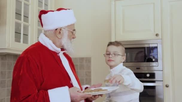 Santa sedí na kuchyňský nábytek a malého chlapce jíst sušenky spolu v kuchyni.