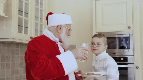 Santa sedí na kuchyňský nábytek a navrhnout mléko chlapce, který mu sedí. Dítě odmítl pít mléko. Stařec a chlapec jíst sušenky dohromady.