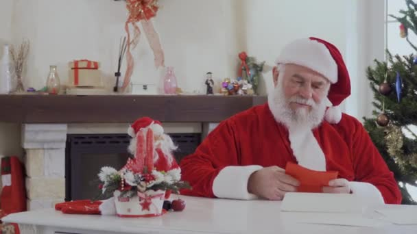 Kedves Mikulás látszó piros ruha, világos, berendezett fenyő és a kandalló közelében karácsonyi levél szól. Öreg ember boldog és mosolyog. Az asztalon van két piros gyertyát, kis alak, Santa