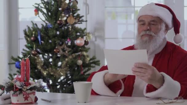 Kedves Mikulás látszó piros ruha, világos, berendezett fenyő és a kandalló közelében karácsonyi levél szól. Öreg ember boldog és mosolyog. Az asztalon van két piros gyertyát, a kupa és a több fehér
