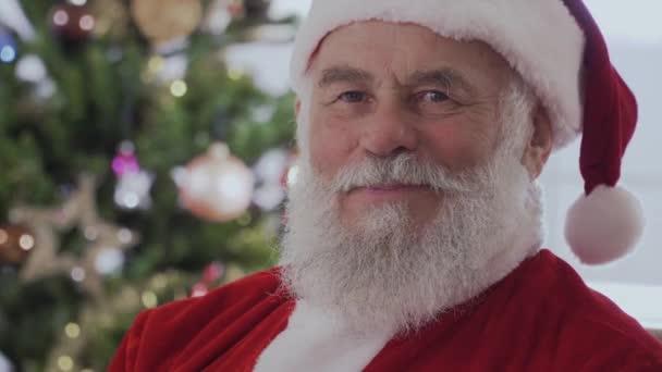 Mikulás egy piros kalap, pompon és karácsonyi jelmez ül, és nevet.