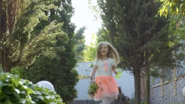 Beautiful little girl in lovely dress run on the path among trees in the garden with basket of flowers in hand. Golden hair of cute child shine on the sun.