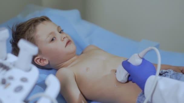 Doktor se ultrasonografie břicha malého chlapce. Dítě na recepci v lékaře