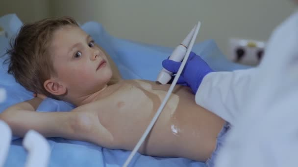 Doctor make ultrasonography of heart of little boy. Child at the reception in the doctor.
