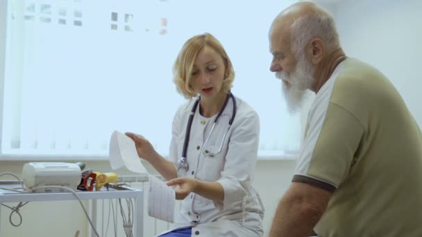 Doctor show results of electrocardiography to senior man. Old man has problems in heart and come to the reception to cardiologist.